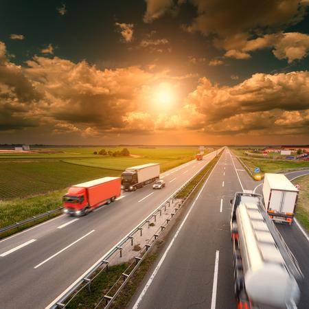Muchos camiones de conducción en el desenfoque de movimiento en la autopista hacia el sol poniente. Hora punta en la autopista cerca de Belgrado - Serbia. Foto de archivo - 44653311