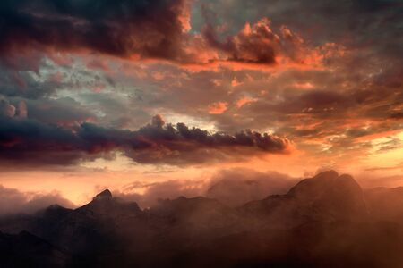 Fiery sunset over the mountain peaks with dramatic cloud formation. National Park Durmitor - Montenegro. Imagens