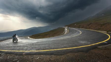 Motorrad fahren in Richtung der Sturm am höchsten und gefährlichsten Asphaltstraße in Rumänien. Trans Autobahn. Standard-Bild - 46087389