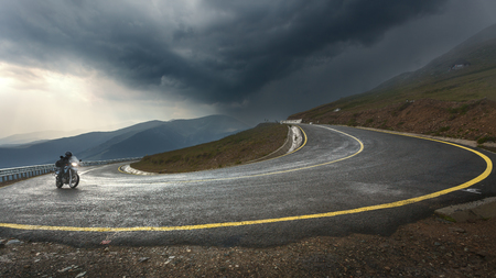 MOTORCYCLES: Riding a motorcycle toward the storm at the highest and most dangerous asphalt road in Romania. Transalpina highway.
