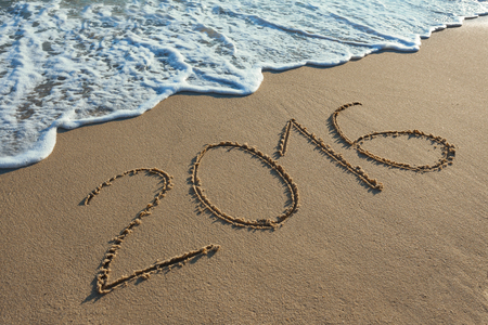 happy holidays: Number 2016 handwritten on seashore sand. Concept of upcoming new year and passing of time. Stock Photo