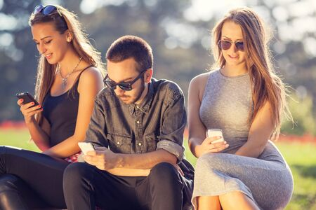 youth group: Communication concept. Group of young hipster friends playing with your mobile phones, each for himself. Stock Photo