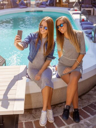 party people: Friendship - lifestyle concept. Two young and cheerful girls having fun and taking selfie near the pool in cafe.