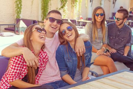 arms around: Friendship - lifestyle concept. Group of young and cheerful friends having fun near pool in the cafe.Young boy put arms around each other of his female friends. Stock Photo