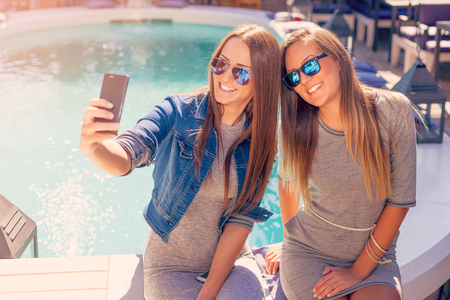 the trendy: Friendship - lifestyle concept. Two young and cheerful girls having fun and taking selfie near the pool in cafe.
