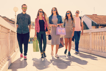 Friendship and shopping concept. Friends walking on the bridge in the city - and three young women with shopping bags. Imagens