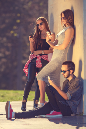 young friends: Communication concept. Group of young hipster friends playing with your mobile phones, each for himself. Stock Photo