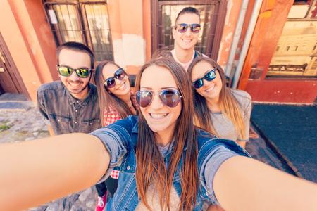 Vriendschap en zomervakantie concept. Groep tieners hebben van goede plezier op de straten van de stad maken van een selfie. Stockfoto
