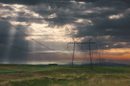 penetrate: Distribution poles with high voltage wires, early in the morning with dramatic sky and sun rays that penetrate through the menacing clouds. Deliblato sands, Serbia.