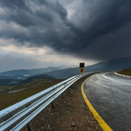 storm: Part of the road with sheet metal protective fence and yellow line. Transalpina road at stormy weather in Romania. Stock Photo