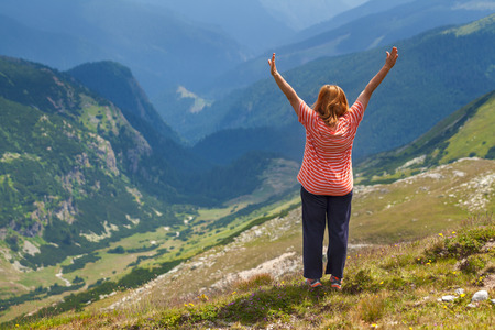 vastness: Women hiker standing on a summit cheering elated with arms raised in the sky towards the great valley in background. Success, winning, victory concept.