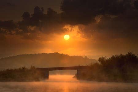 bridge in nature: Peaceful nature scene on the lake with bridge at misty dawn towards the rising sun. Knic lake, Serbia.