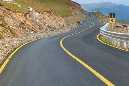 signos de precaucion: Transalpina zigzag camino en el día, la carretera más alta y la más peligrosa de asfalto en Rumania.