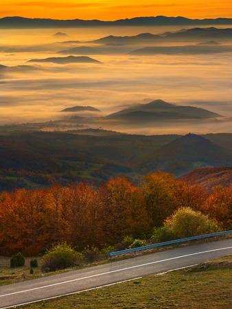 ambiance: Empty road in idyllic mountaian scenery at autumn ambiance illuminated by morning sunlight. Mountain Golija, Serbia. Stock Photo