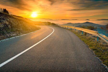 Driving on an empty asphalt road towards the rising sun at autumn season in mountain area. Mountain Golija, Serbia. Imagens