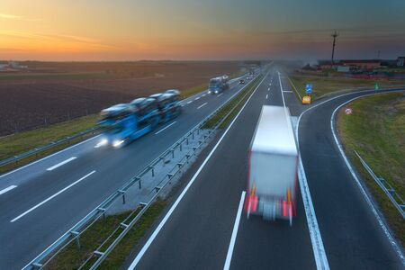 autobahn: Many trucks driving in motion blur on the freeway at beautiful sunset. Rush hour on the motorway near Belgrade - Serbia.