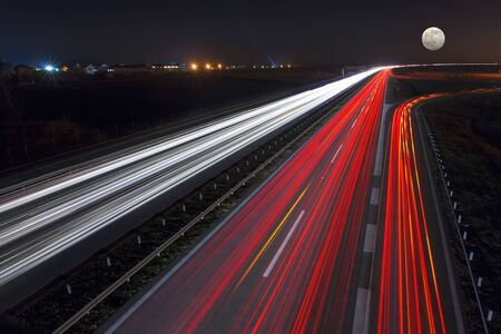 city road: Driving on highway at night near Belgrade - Serbia. Llight trails on motorway at night of full moon, long exposure abstract photograph.