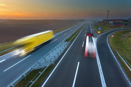 motorway: Two trucks driving in motion blur on the freeway at beautiful sunset. Rush hour on the motorway near Belgrade - Serbia. Stock Photo