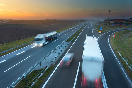 red white blue: Many trucks driving in motion blur on the freeway at beautiful sunset. Rush hour on the highway near Belgrade - Serbia. Stock Photo