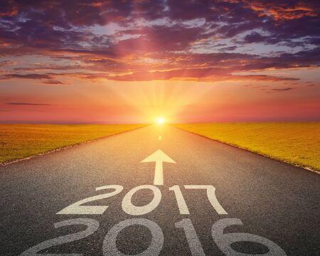 Das Fahren auf einer leeren Straße in Richtung der untergehenden Sonne auf den kommenden Jahren 2017 und hinter alten 2016 zu verlassen. Standard-Bild - 52202100