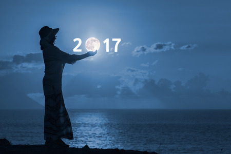Woman standing on hill near the ocean and holding moon in hands. Concept of upcoming 2017 new year and passing of time.