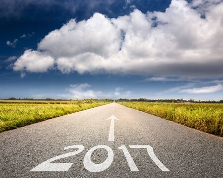 Driving on an empty road towards the big cloud to upcoming 2017 through idyllic scenery. Concept for success and passing time. Stock Photo