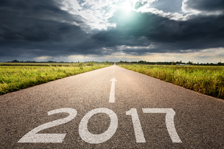 Driving on an empty road towards the sun and big black cloud to upcoming 2017. Concept for success and passing time. Imagens