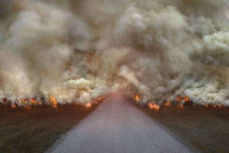 Driving on an empty road to the large fire and smoke. Concept for global warming. Imagens