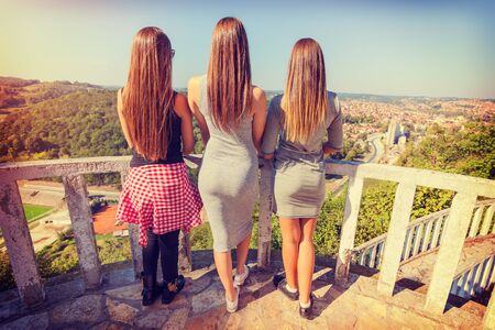 people from behind: Group of young girls having fun and watching panorama of the city from the lookout. Friendship - lifestyle concept. Stock Photo