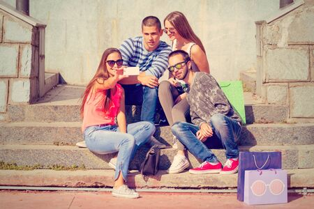 stylish men: Friendship concept. Smiling group of friends having fun andtaking selfie.