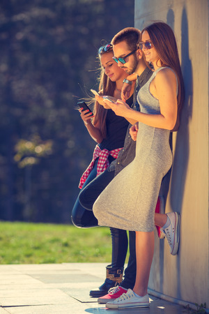 mobile communication: Communication concept. Group of young hipster friends playing with your mobile phones, each for himself. Stock Photo