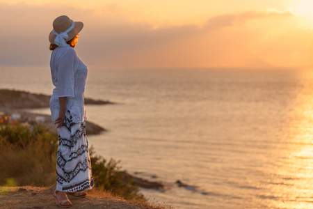 watching: Woman in retro hat standing and watching towards the sun peaceful sunset during your holiday on Greek coast of Aegean sea.