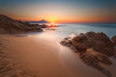Beautiful sunrise on Greek coast of Aegean sea with holy mountain Athos in background. Long exposure shot with motion blur effect. Chalkidiki, Greece.