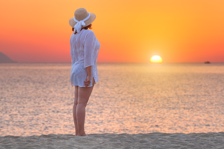 woman sunset: Woman in retro hat standing towards the sun at peaceful beach sunset during your holiday on Greek coast of Aegean sea.