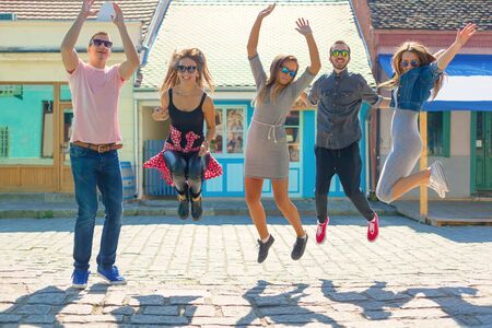Friendship and summer holidays concept. Group of teenagers having fun on the city streets jumping up in air.