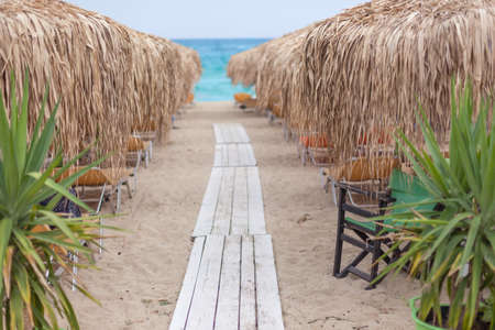 tiefe: Path to the sea through beach chairs and thatched umbrellas on the beautiful beach at morning. Shallow depth of field. Greek cost of Aegean sea. Lizenzfreie Bilder