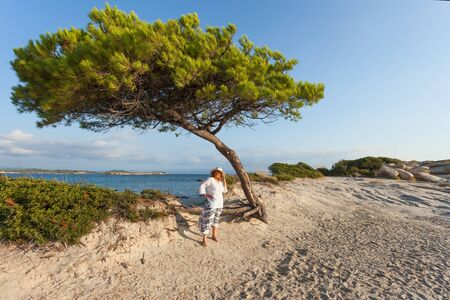 Woman standing under the pine wood in the windy day at sandy beach during your holiday on Greek coast of Aegean sea. Stock Photo