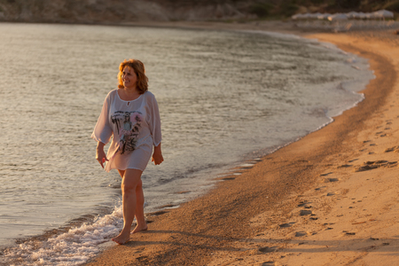 cinematic: Woman walking on beautiful sandy beach at sunset during your holiday on Greek coast of Aegean sea.
