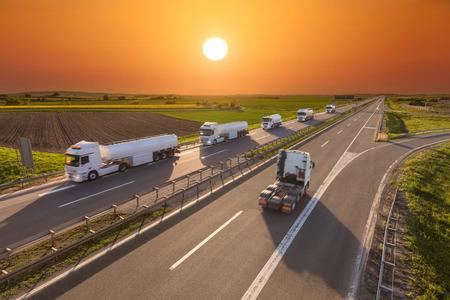 Viele weiße Benzintankwagen in der Linie und eine ohne Anhänger in Richtung der Sonne zu fahren. Schnelle Bewegungsunschärfe Fahrt auf der Autobahn bei Sonnenuntergang. Fracht-Szene auf der Autobahn in der Nähe von Belgrad, Serbien. Standard-Bild - 55392155