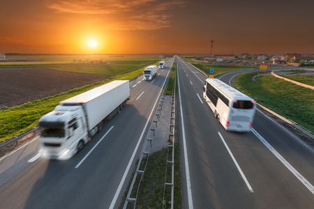 Many white trucks in line and fast travel bus driving towards the sun. Speed blurred motion drive on the freeway at beautiful sunset. Transport travel scene on the motorway near Belgrade, Serbia. Stock Photo
