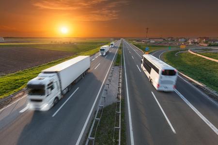 Vele witte vrachtauto's in de rij en snel reizen bus rijden naar de zon. Speed wazig beweging rijden op de snelweg bij mooie zonsondergang. Vervoer reizen scène op de snelweg in de buurt van Belgrado, Servië.