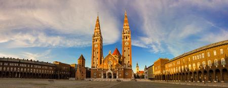 Panorama der Doppel spired Kirche am Domplatz in Szeged. Die Votiv-Kirche und der Kathedrale Notre-Dame von Ungarn bei Sonnenuntergang. Viertgrößte Gebäude in Ungarn mit zwei großen Türmen beide 91 m hoch. Standard-Bild - 55392171