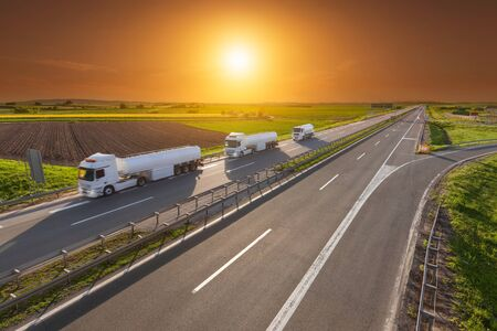 move ahead: Three white gasoline tanker trucks in line driving towards the sun. Fast gasoline delivery on the freeway at beautiful sunset. Freight scene on the motorway near Belgrade, Serbia. Stock Photo