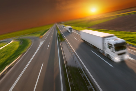 reefer: Three new reefer trucks in a row at left side driving on freeway with speed blurred motion. Freight scene on the motorway. Speed concept for temperature controlled truck.