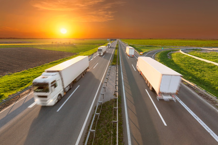 Temperature controlled trucks driving towards the sun. Fast blurred motion drive on the freeway at beautiful sunset. Freight scene on the motorway near Belgrade, Serbia.