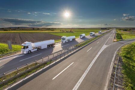 hilera: Muchos camiones cisterna de gasolina blanca en la línea de conducción hacia el sol. la entrega rápida de gasolina en la autopista en un hermoso día idílico. escena de la carga en la autopista cerca de Belgrado, Serbia.
