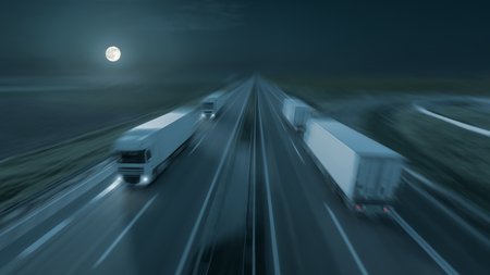 multiple lane highway: New temperature controlled trucks driving fast towards the moon at night. Speed blurred motion drive on the freeway. Freight scene on the motorway as speed concept. Stock Photo