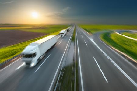 hilera: Tres nuevos camiones en una fila que conduce rápidamente hacia el sol. Velocidad de la unidad de movimiento borrosa en la autopista. escena de la carga en la autopista cerca de Belgrado, Serbia. concepto de velocidad.
