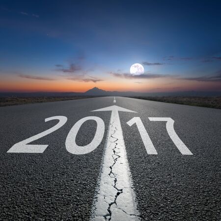 the passing of time: Driving on an empty road towards the setting moon to upcoming new 2017 year. Concept for success and passing time.
