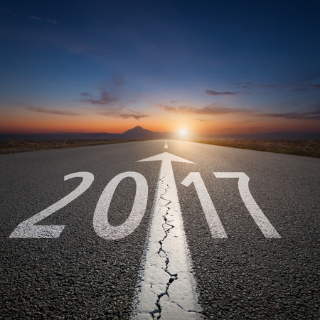 Driving on an empty road towards the setting sun to upcoming new 2017 year. Concept for success and passing time.
